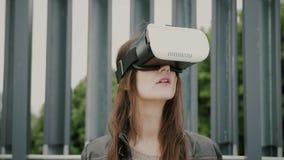 Brunettkvinnaflickan med vinkande hår använder virtuell verklighetexponeringsglas i det stads- utrymmet 4K royaltyfri fotografi