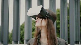 Brunettkvinnaflickan med vinkande hår använder virtuell verklighetexponeringsglas i det stads- utrymmet 4K arkivbild