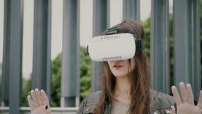 Brunettkvinnaflickan med vinkande hår använder virtuell verklighetexponeringsglas i det stads- utrymmet 4K Royaltyfri Bild
