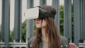 Brunettkvinnaflickan med vinkande hår använder virtuell verklighetexponeringsglas i det stads- utrymmet 4K Arkivbilder