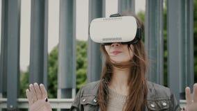 Brunettkvinnaflickan med vinkande hår använder virtuell verklighetexponeringsglas i det stads- utrymmet 4K Arkivfoton