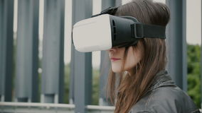Brunettkvinnaflickan med vinkande hår använder virtuell verklighetexponeringsglas i det stads- utrymmet 4K royaltyfria foton