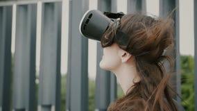 Brunettkvinnaflickan med vinkande hår använder virtuell verklighetexponeringsglas i det stads- utrymmet 4K Royaltyfri Foto