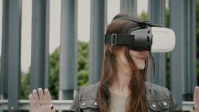 Brunettkvinnaflickan med vinkande hår använder virtuell verklighetexponeringsglas i det stads- utrymmet 4K Royaltyfria Bilder