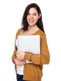 Brunettkvinnahåll med bärbara datorn Royaltyfri Fotografi