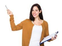Brunettkvinnahåll med mappblocket och pennpunkt upp Arkivfoton