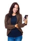 Brunettkvinnahåll med mobiltelefonen Fotografering för Bildbyråer