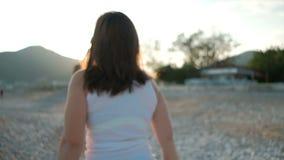 Brunettkvinnan är glad att beskåda solljus på kusten av havet i ferie arkivfilmer