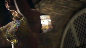 Brunettkvinnan dansar magdans i restaurang i ljus av soffits stock video