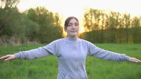 Brunettkvinnan gör gymnastikövningar i fältet på soluppgång stock video