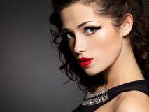 Brunettkvinnan med danar makeup och röda kanter royaltyfria foton
