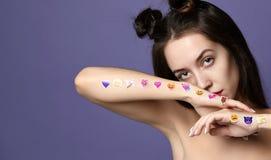 Brunettkvinnan med populär social emoji ler klistermärkear på hennes händer förargar olyckligt på lilor arkivfoto
