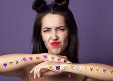 Brunettkvinnan med populär social emoji ler klistermärkear på hennes händer förargar olyckligt på lilor fotografering för bildbyråer