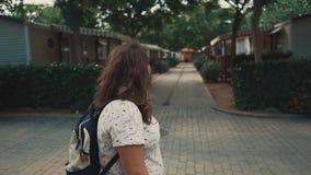 Brunettkvinnan med solglasögon beundrar arkitektur och naturen av den lilla staden stock video