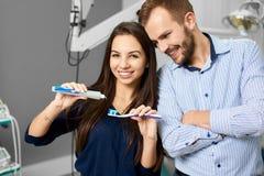 Brunettkvinnan pressar en tandkräm, och en smart man håller ögonen på henne att göra denna i ett modernt vitt tand- kontor royaltyfri bild