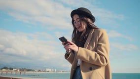 Brunettkvinnan smsar sms vid smartphonen i sjösidaområde i soligt väder stock video