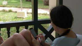 Brunettkvinnan som använder mobiltelefonen för pratstund i samkväm, knyter kontakt på utomhus- balkong arkivfilmer