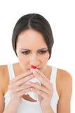Brunettkvinnan som har en näsa, blöder Arkivbild