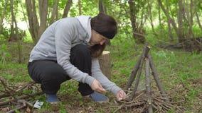 Brunettkvinnan tänder en brand i skogen arkivfilmer