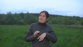 Brunettkvinnan vinkar av en jobbig mygga i aftonen lager videofilmer
