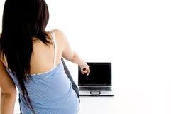 brunettkvinnligbärbar dator som pekar deltagaren till Arkivbild