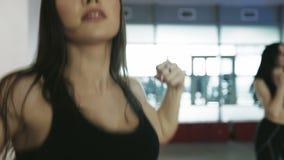 Brunettkvinnor som gör övningar i konditionidrottshall långsam rörelse stock video