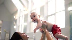 Brunettmodern med behandla som ett barn sondyken som är undervattens- med gyckel i simbassäng Sund livsstil, aktiv förälder, simn arkivfilmer