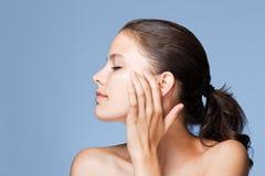Brunettskönhet genom att använda lotion. Royaltyfria Bilder