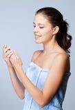 Brunettskönhet genom att använda lotion. Royaltyfri Bild