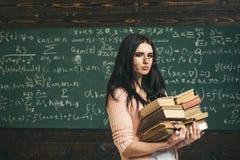 Brunettstudent som framme går med två högar av böcker av det gröna brädet mycket av handstil Förbereda sig för matematikstudent royaltyfri foto