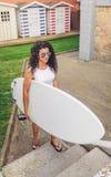 Brunettsurfarekvinna med den bästa hållande surfingbrädan Arkivbilder