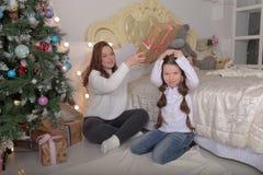 Brunettsysterflickor med julklappar i vita tröjor som har gyckel royaltyfri foto