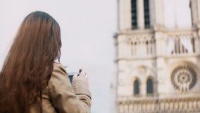 Brunetttonåring som tar fotoet av Notre Dame på retro filmkamera som undersöker de berömda ställena av Paris, Frankrike lager videofilmer
