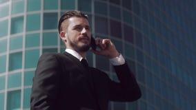 Brunhårig affärsman som utomhus talar på telefonen stock video