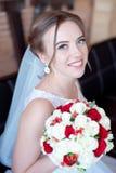 Brunhårig brud med den klassiska bröllopfrisyren som ler ta bröllopbukett i henne händer Arkivbild