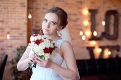 Brunhårig brud med den klassiska bröllopfrisyren som ler ta bröllopbukett i henne händer royaltyfri bild