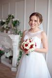 Brunhårig brud med den klassiska bröllopfrisyren som ler ta bröllopbukett i henne händer royaltyfri foto