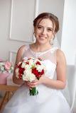 Brunhårig brud med den klassiska bröllopfrisyren som ler ta bröllopbukett i henne händer royaltyfria bilder