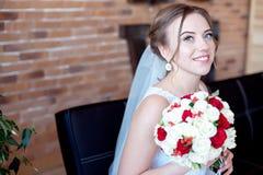 Brunhårig brud med den klassiska bröllopfrisyren som ler ta bröllopbukett i henne händer Arkivbilder
