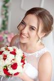 Brunhårig brud med den klassiska bröllopfrisyren som ler ta bröllopbukett i henne händer royaltyfri fotografi