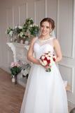 Brunhårig brud med den klassiska bröllopfrisyren som ler ta bröllopbukett i henne händer royaltyfria foton