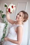 Brunhårig brud med den klassiska bröllopfrisyren som ler ta bröllopbukett i henne händer Arkivfoto