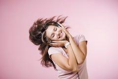 Brunhårig flicka med hörlurar som lyssnar till musik med stängda ögon på rosa bakgrund arkivfoto