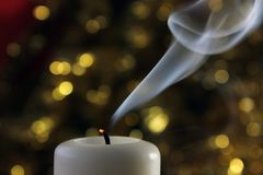 Extinguished candle with smoke on green twinkling lights on the background. Stock Photos