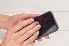 Brunn-ansade kvinnlighänder med smartphonen royaltyfri foto