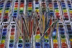 Brunn-använda pannor för konstnärPaintbrushes Arrayed Across färgrika vattenfärg arkivbild