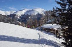 Brunnach Ski Resort, St Oswald, Carinthia, Österrike - Januari 20, 2019: En kabin bredvid skidar lutningen med skidåkare framme, fotografering för bildbyråer