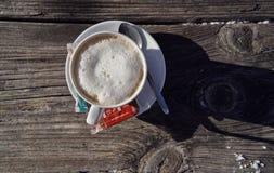 Brunnach Ski Resort, St Oswald, Carinthia, Österrike - Januari 20, 2019: Kopp kaffe som fångas på en gammal trätabell arkivfoto