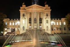 Brunnen auf dem Hintergrund der historischen Gebäude nachts Stockfotografie