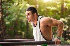 Brunnen byggde den muskulösa mannen som utomhus gör en fysisk övning arkivfoto